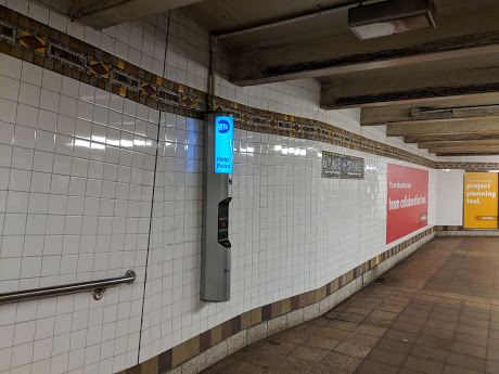 A help phone on the wall in the NYC subway